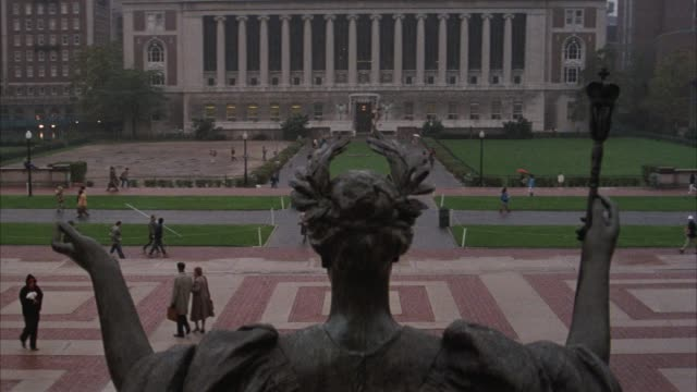 wide angle of butler library at columbia university. library building is framed by upraised arms of bronze alma mater statue, aka roman goddess minerva. see pedestrians walking and talking in plaza area in front of low library. plaza or quad includes patt - ivy league university stock videos and b-roll footage