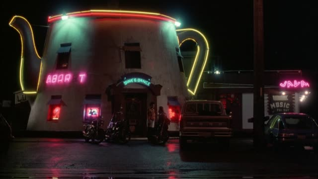 """stockvideo's en b-roll-footage met wide angle of restaurant or bar. building is shaped like a giant coffee pot or teapot with spout and handle outlined in neon lights. neon signs for """"abar-t"""" and """"dine & dance""""  and """"java"""" and sign for """" music"""" on right. truck,  car, and motorcycles in par - bar gebouw"""