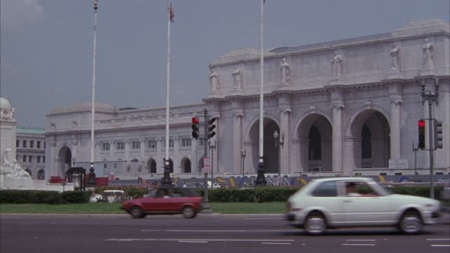 wide angle of union station in washington dc. union station is a late 19th century beaux arts style train station in washington dc with many arches. see cars drive through street intersection and traffic signals in foreground. shot pans from left to right - embassy stock videos & royalty-free footage