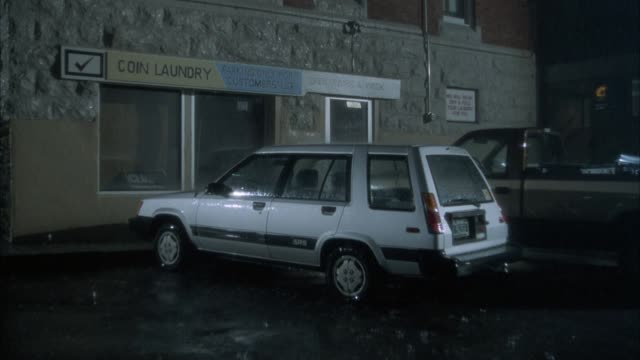 """est. medium angle of parked cars outside closed laundromat. see white convertible pull up to parking lot. see rain fall. see sign saying """"coin laundry"""" in background. - launderette stock videos and b-roll footage"""