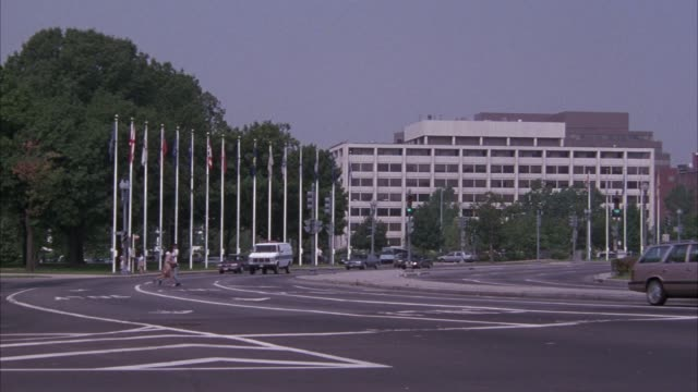 pan left to right of cars driving through intersection outside of union station. union station is a late 19th century beaux arts style train station in washington dc with many arches.  shot pans from left to right of police van driving towards pov and exi - embassy stock videos & royalty-free footage