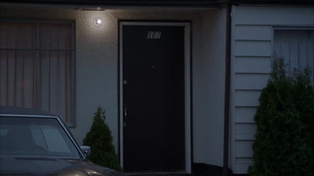 zoom in hotel or apartment door and exterior. see white siding, window on either side of door. see  light on near door and inside behind curtains. pontiac gto parked in front of entrance. - ポンティアック点の映像素材/bロール