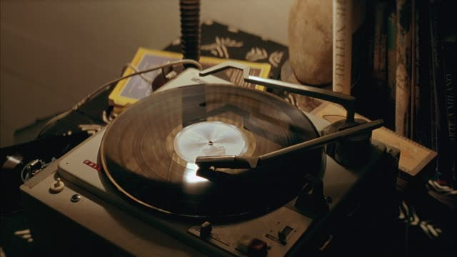 vidéos et rushes de close angle of record player sitting on covered tabletop. see record spinning. - platine de disque vinyle