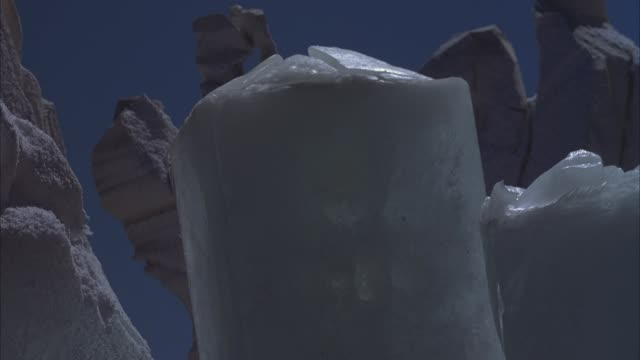medium angle of blocks of ice. see long jagged rocks in background. could be desert rocks. clear blue skies. rocks and ice suddenly explode and debris flies everywhere. explosions. - rock stock videos & royalty-free footage