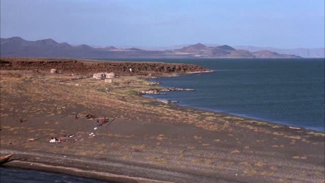 vídeos y material grabado en eventos de stock de aerial of peninsula and ocean area. see huts lined up along shoreline. - península