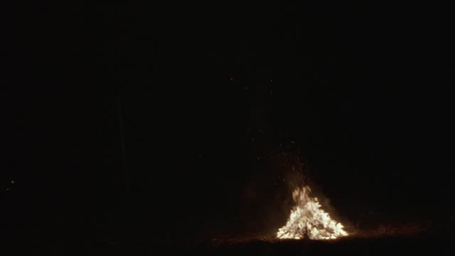 medium angle of bonfire. see wood stacked in a pyramid supporting fire. see lights from vehicles passing from left to right in distance. bonfire is burning near telephone pole. - vedbrasa bildbanksvideor och videomaterial från bakom kulisserna