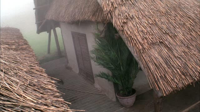 high angle down of thatched roof houses. see fierce wind blow dust around frame. see debris fly from offscreen. - thatched roof stock videos & royalty-free footage