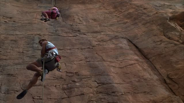up angle of two mountain climbers hanging by rope next to rust colored rock wall. see rope jerk down as lower climber looks down in fear. see lower climber watch higher climber flail and kick. - corda video stock e b–roll