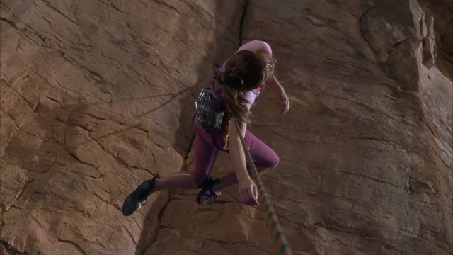 MEDIUM ANGLE OF FEMALE ROCK OR MOUNTAIN CLIMBER DANGLING FROM ROPE NEXT TO RUST COLORED ROCK WALL. SEE CLIMBER TWIST AND FLAIL, TRYING TO REACH WALL.