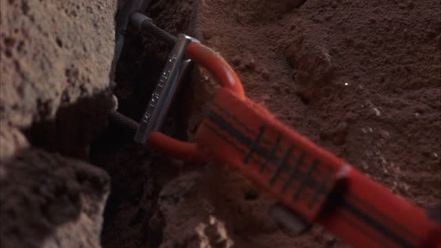 CLOSE ANGLE OF ROCK OR MOUNTAIN CLIMBING GEAR OR CAMMING UNIT STUCK INTO CRACK OF RUST COLORED ROCK WALL. SEE RED STRAPS OF CAMMING UNIT PULLED TAUT. SEE CAMMING UNIT SLIP HALFWAY OUT OF CRACK AND STOP. POV SHAKES.