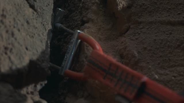 CLOSE ANGLE OF ROCK OR MOUNTAIN CLIMBING GEAR OR CAMMING UNIT STUCK INTO CRACK OF RUST COLORED ROCK WALL. SEE RED STRAPS OF CAMMING UNIT PULLED TAUT. SEE CAMMING UNIT SLIP HALFWAY OUT OF CRACK AND STOP.