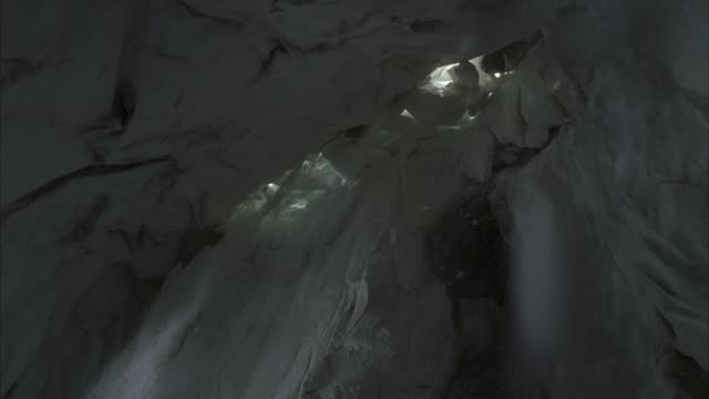 up angle of ceiling of ice or snow cave. see sunlight through large blocks of ice filling gap in ceiling. see snow fall toward pov. see snow stream through cracks between ice blocks in gap. see light blocked out from behind ice blocks and snow stop. - ice stock videos & royalty-free footage
