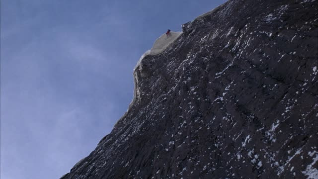 up angle of rock wall or cliff of snowy mountain. huge block of ice or snow falls toward camera and covers frame. could be avalanche. action. - mountain peak stock videos & royalty-free footage