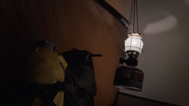 medium angle of interior of tent. see gas lamp hanging on right and oxygen tank attached to back pack on left. tent shakes constantly from exterior, could be windy or storm outside. - oxygen tank stock videos and b-roll footage
