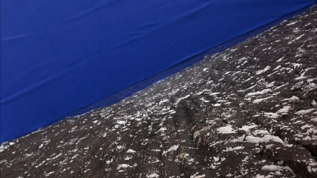 HIGH ANGLE DOWN OF ROCK FACE WITH BLUE SCREEN TARP ABOVE ROCK, SNOW ON MOUNTAIN. LARGE ROCK FALLS ONTO BLUE SCREEN.