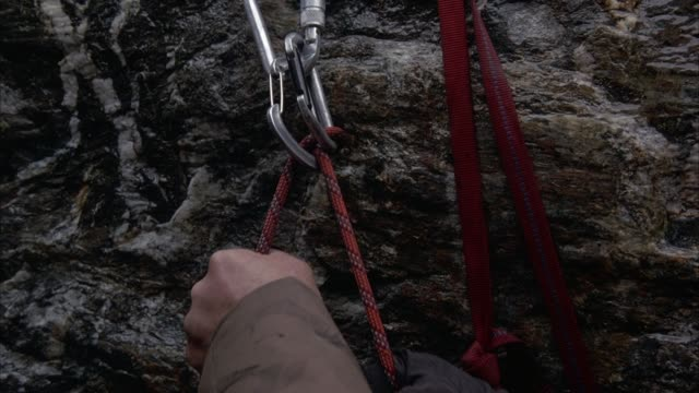 CLOSE ANGLE OF RED ROPE THREADED THROUGH CARABINERS OR MOUNTAIN CLIMBING TOOLS OR GEAR ATTACHED TO GREY ROCK WALL. SEE RED STRAPS HANGING AT RIGHT. SEE ONE GLOVED AND ONE BARE HAND FEEDING RED ROPE THROUGH CARABINER TOWARD RIGHT.