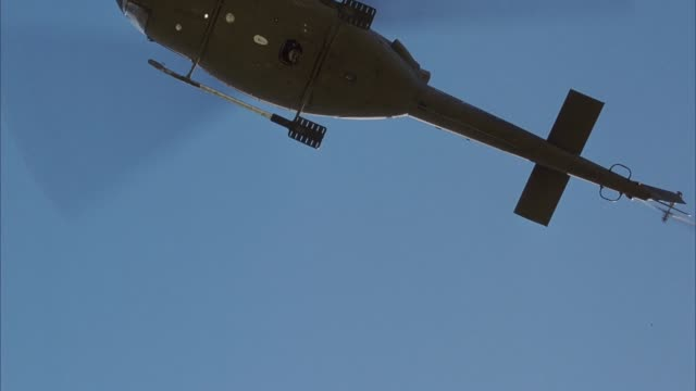 vídeos de stock e filmes b-roll de up angle of bottom of army green helicopter as it hovers over pov. see white light or led flashing at base of helicopter. see clear blue sky in background. - pairar