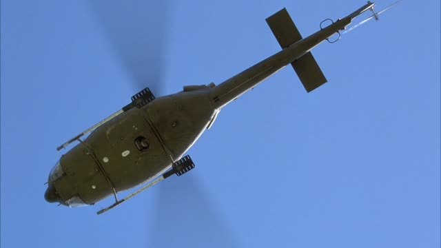 vidéos et rushes de up angle of bottom of army green helicopter hovering overhead. white light or led at base of helicopter flashing. helicopter turns 90 degrees clockwise away from pov. - armée de terre
