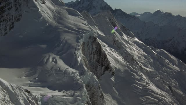 AERIAL ALONG SNOW COVERED MOUNTAIN RANGE. FOCUS ON SMALL SNOW HILL ON SLOPE AS POV TURNS CLOCKWISE. SEE SNOW COVERED MOUNTAINS BELOW AND IN BACKGROUND.