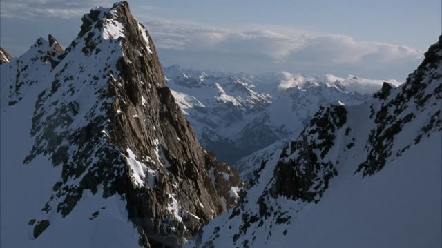 aerial of snow covered mountain ridge. see lower mountain peaks with lower slopes obstructed by sea of cumulus clouds in background. see army green helicopter fly from bottom between gap and over ridge. see helicopter exit down. see high snowy peak at rig - snowcapped mountain stock videos & royalty-free footage