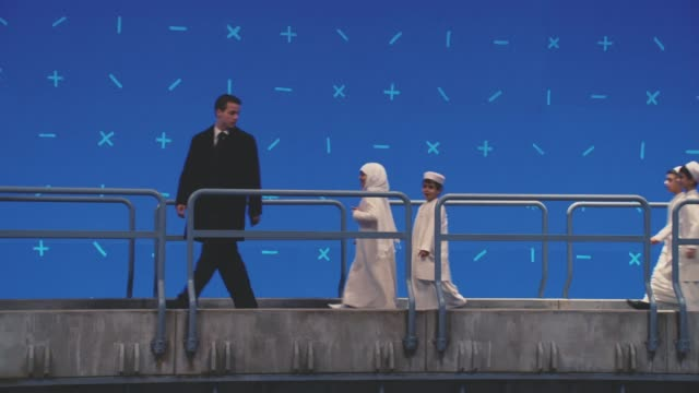 medium angle of upper class or royal middle eastern family walking across metal catwalk, ramp, or platform. blue screen in bg. men and women wear robes. security guards and soldiers visible. - wachmann stock-videos und b-roll-filmmaterial