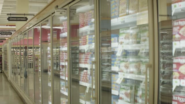 medium angle of grocery store or market. aisles partially visible. freezer section. - refrigerated section stock videos & royalty-free footage