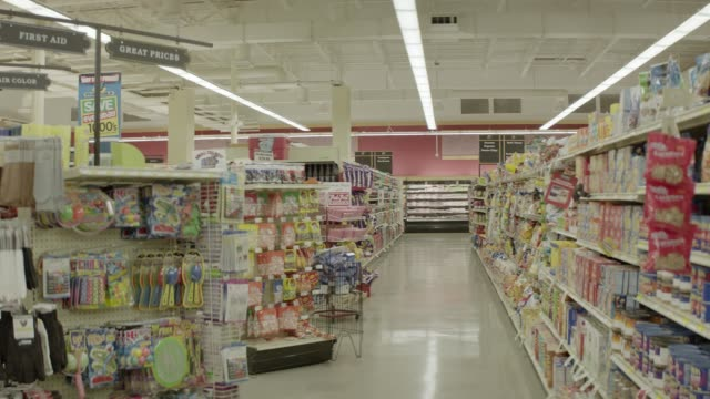 wide angle of grocery store or market. aisles visible with food, candy, and toys. meat freezer visible in bg. man walks down aisle with case of beer. - aisle stock videos and b-roll footage