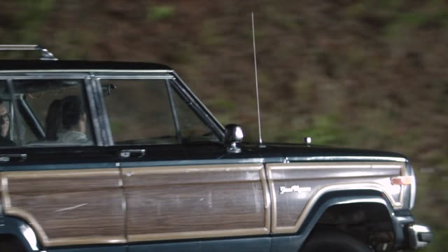 MEDIUM ANGLE OF JEEP GRAND WAGONEER ATTEMPTING TURN OR EVASIVE MANEUVER. COULD BE CAR STUNTS. COULD BE COLLISION OR ACCIDENT. COULD BE SWERVING OR SPINNING.