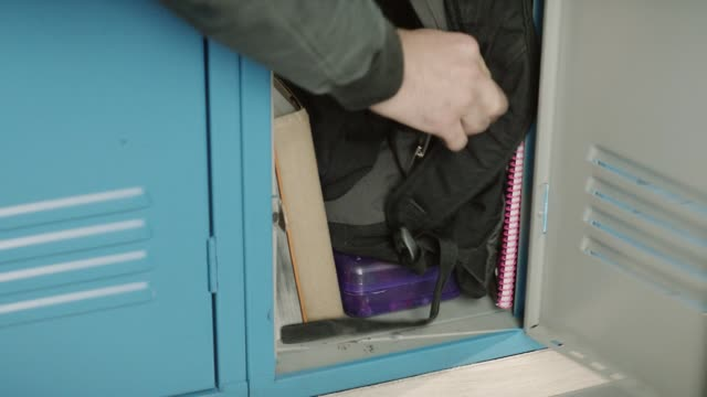 close angle of person putting school backpack or book bag into locker. textbooks, notebooks, and pencil case visible. could be student. - rucksack stock videos & royalty-free footage