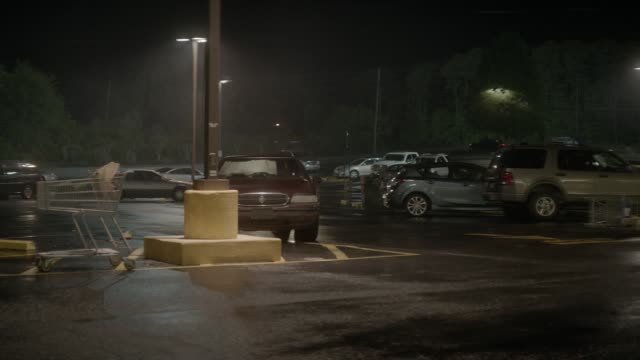 medium angle moving pov of grocery store parking lot. jeep grand wagoneer drives erratically, hits parked cars, and overturns. could be crash, accident, or collision. car stunts. shopping carts visible. - parken stock-videos und b-roll-filmmaterial