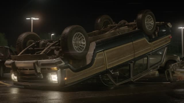 medium angle of overturned jeep grand wagoneer suv in parking lot. other cars and shopping cart partially visible. could be crash, accident, or collision. - aufprall stock-videos und b-roll-filmmaterial