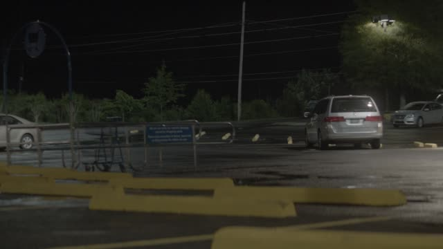 pan right to left of jeep grand wagoneer driving erratically through parking lot. cars and shopping carts visible. could be grocery store parking lot. - sports utility vehicle stock-videos und b-roll-filmmaterial