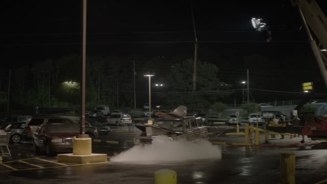 stockvideo's en b-roll-footage met wide angle of jeep grand wagoneer in parking lot as pipe or tree is pulled out of smashed hood. could be grocery store parking lot. cars, suvs, and shopping carts visible. smoke or mist emits from hood of jeep. - motorkap