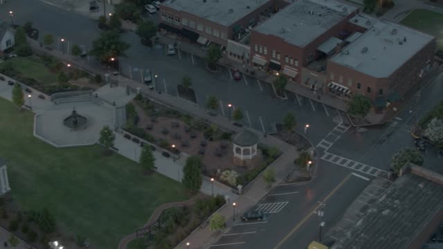 stockvideo's en b-roll-footage met aerial of memorial park with fountain in small town. brick buildings, storeffronts, and shops visible. - memorial