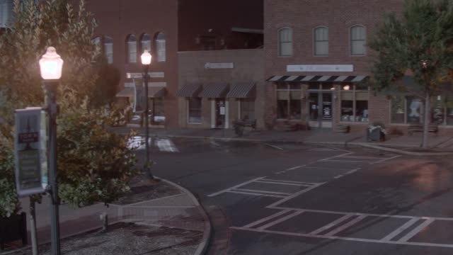 aerial moving pov of small town streets. brick buildings, shops, and storefronts visble. lincoln continetnal mark iii visible in street. camera partially circles car. - lincoln town car stock videos and b-roll footage