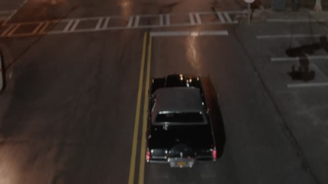 aerial moving pov of lincoln contintental mark iii car driving on or through small town streets. brick buildings, shops, and storefronts visble. small park with gazeebo visible in fg. - lincoln town car stock videos and b-roll footage