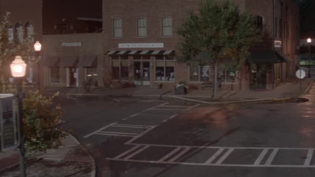 aerial moving pov of small town streets. brick buildings, shops, and storefronts visble. lincoln continetnal mark iii visible in street. camera partially circles car and pans up as car swerves down street away from camera. domed city hall or courthouse bu - lincoln town car stock videos and b-roll footage