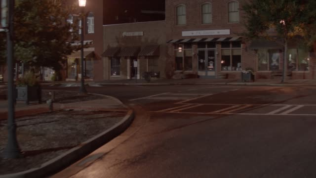 vidéos et rushes de aerial moving pov of small town streets. brick buildings, shops, and storefronts visble. lincoln continetnal mark iii visible in street. camera partially circles car and pans up as car swerves down street away from camera. domed city hall or courthouse bu - town hall
