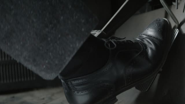 close angle of foot in business shoe stepping on accelerator pedal in bus. air brake pedal visible. series. - brake stock videos & royalty-free footage