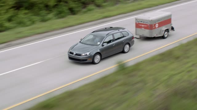 stockvideo's en b-roll-footage met aerial front angle of car driving through rural area or country on freeway or highway from right to left. car towing u-haul trailer. - aanhangwagen