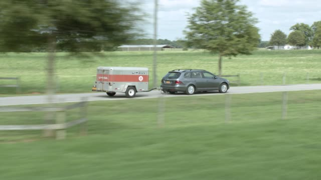 stockvideo's en b-roll-footage met aerial  car driving left to right through countryside or rural area. car tows u-haul trailer. could be farmland. trees or woods visible. some houses and fences vsibile. - aanhangwagen