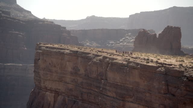 wide angle of butte or mesa. could be desert. group of people running in line from right to left. could be soldiers or cadets. could be training exercise. - butte rocky outcrop stock videos & royalty-free footage