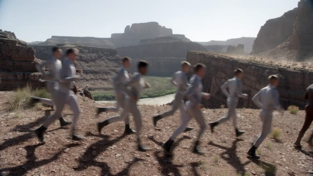 medium angle of group of people running in line from left to right in desert, butte, or mesa. could be soldiers or cadets. could be training exercise. river and valley visible in bg. - butte rocky outcrop stock videos & royalty-free footage