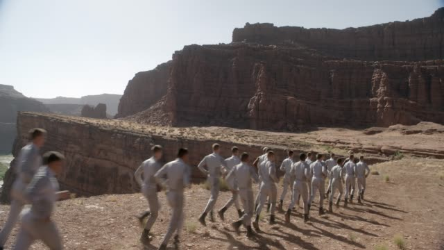 vidéos et rushes de medium angle of group of people running in line from left to right in desert, butte, or mesa. could be soldiers or cadets. could be training exercise. river and valley visible in bg. - élève officier