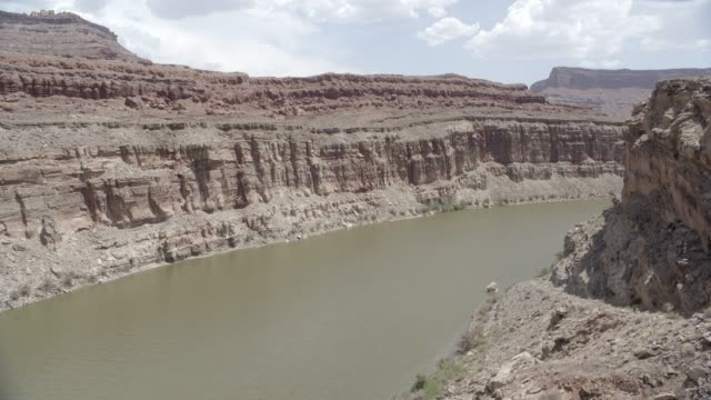 medium angle of river in desert canyon or valley. could be mesa or butte. - butte rocky outcrop stock videos and b-roll footage