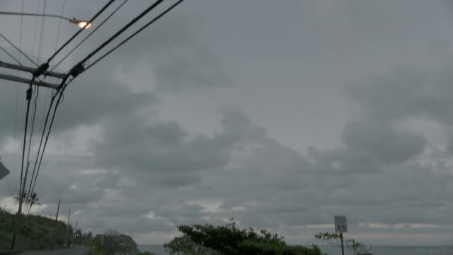 """pan down and left to right from telephone, power, or electric lines to sign reading """"andersen air force base guam"""". camera zooms in on sign. ocean visible left of camera. could be costal road. - グアム点の映像素材/bロール"""