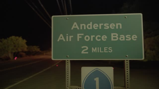 """zoom in close angle of military base exit sign for """"anderson air force base guam"""". trees and telephone, electric, or power lines visible. - グアム点の映像素材/bロール"""
