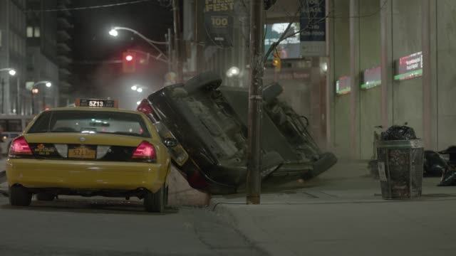 medium angle of city street people running or fleeing. person on motorbike or scooter flees. car on road flips over taxi. could be disaster, attack, or emergency. could be car stunt, collision, car crash, or car chases. - entrare in collisione video stock e b–roll
