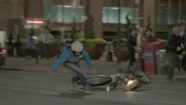 medium angle of person with helmet on bicycle or motorbike on city street fleeing. person falls off bike and runs off in terror. people running or fleeing in panic in bg. could be disaster, emergency, or attack. could be stunt or chase. - stunt stock videos & royalty-free footage