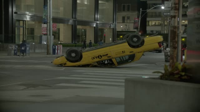 stockvideo's en b-roll-footage met medium angle of overturned taxi in city street and people or pedestrians running in panic. could be disasters, attacks, or emergency. three mini coopers swerve around car and corner. could be car chase. car stunts. - toronto